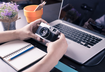 Art Graphic designer and photographer working desk with vintage camera notebook laptop in vitnage tone