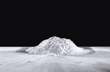 Pile of flour on table against dark background Wall mural