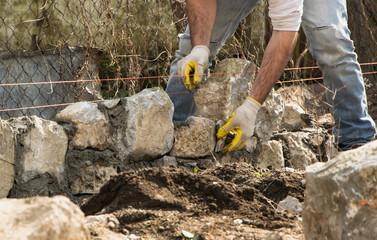 Mason  building a  stone wall