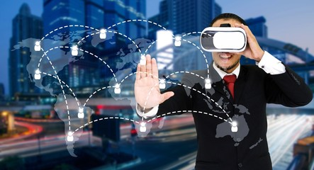 Young asian businessman wearing VR virtual reality headset, business and technology concept for future with world map social media connection on blurred night city