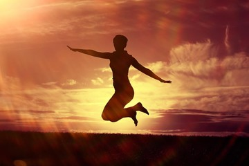 Silhouette of a girl against the sky jumping at sunset, concept of happiness