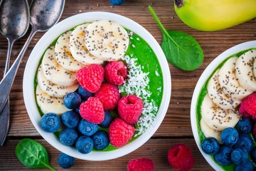 Healthy breakfast bowl: green spinach smoothie with banana, blueberries, raspberries, chia seeds and coconut