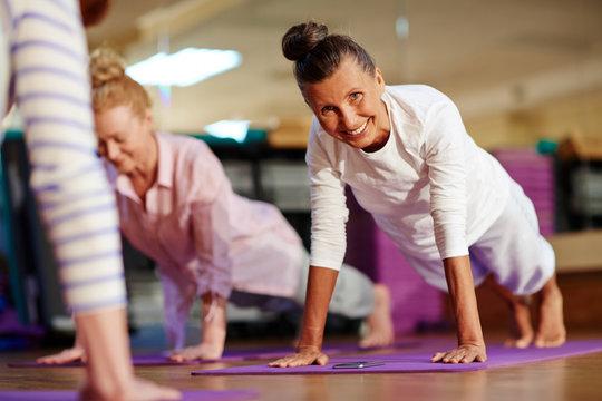 Happy woman doing push-ups on mat