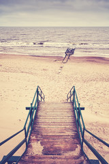 Retro toned picture of stairs on beach, rainy nostalgic mood.