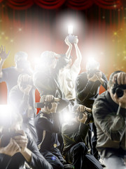 Crowd of paparazzi with flashing cameras in front a flashy background