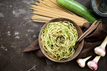 Pasta with zucchini and pesto on dark background. Spaghetti from organic wholegrain flour