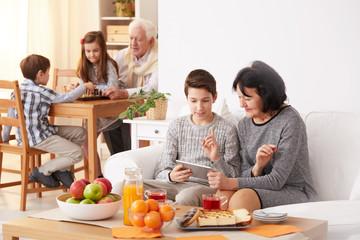 Boy teaching grandma how to use a tablet