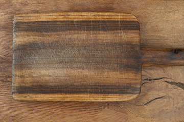 Cutting board on wooden table. Old grunge wooden cutting kitchen desk board background texture top view.