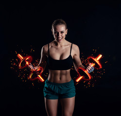 Portrait of a young fitness woman in sportswear doing workout with fiery dumbbells on black background. Tanned sexy athletic girl. A great sporty female body.