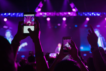 Hand holding smartphone records live music festival with screen