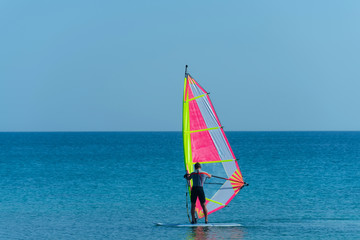 Windsurfer man windsurfing on board with sail in sea