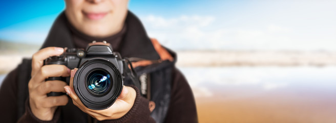 Portrait of unrecognizable female photographer make photography at the sea - panoramic background free space to use.