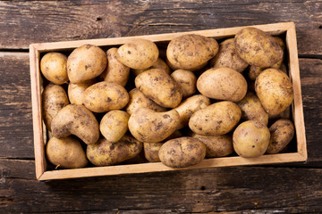 fresh potatoes in wooden box on wooden table
