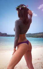 Back view of sensual brunette woman wearing gray long sleeve top, purple underwear bottom and wreath standing on the sandy beach over beautiful sea and blue sky background