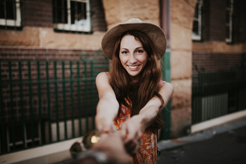 Woman holding boyfriend hand, while taking a photo of her.