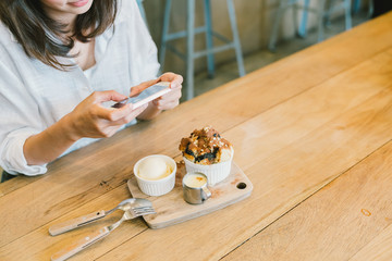 Asian girl taking photo of chocolate toast cake, ice-cream, and milk at coffee shop. Dessert or food photograph hobby. Smartphone or mobile phone photography habit concept. With copy space