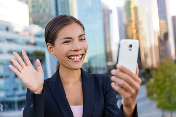 Video chat business meeting concept. Businesswoman taking selfie photo using smart phone app on smartphone for social media smiling happy wearing suit jacket outdoors. Urban female professional.