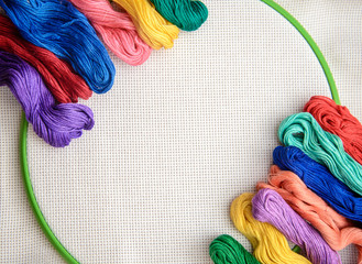 Multicolored embroidery floss on a background of embroidery with white outline