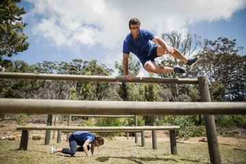 Man and woman jumping over the hurdles during obstacle course