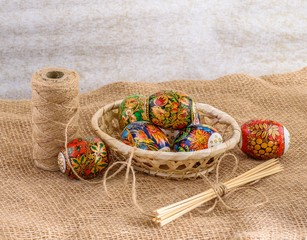 Easter eggs with bright lacquer paintings in a wicker basket on the tablecloth of burlap