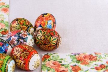 Easter eggs with bright paintings and on a light background of natural tablecloths and coloured serviettes