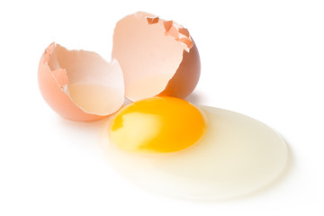 A broken chicken egg lies on a white background with a shell, yolk and spilled protein, isolated
