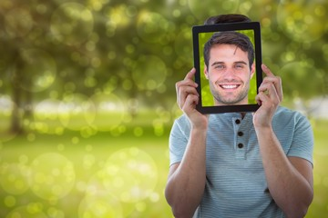 Composite image of man holding digital tablet in front of face