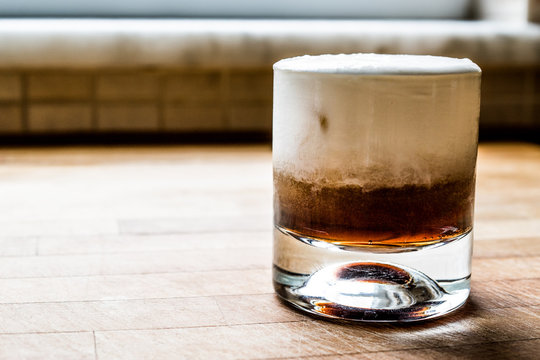 White Russian Cocktail on wooden surface.