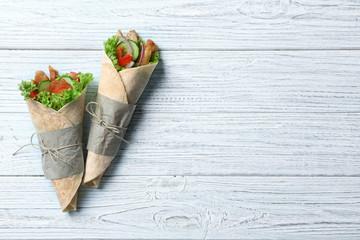 Tasty kebab rolls on white wooden background
