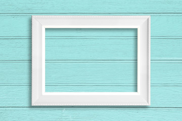 White blank picture frame on wood background.