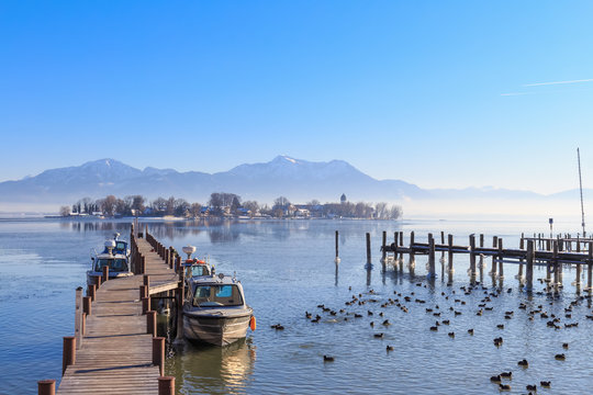 Boats at Jetty in Gstadt, Bavaria, Germany, with Lake Fraueninsel in the background on a cold winter day