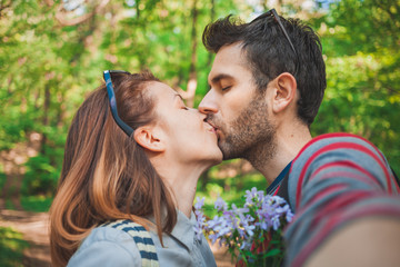 Young couple in love taking a selfie while kissing in the park