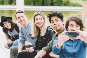 Group of friends multiethnic millennials using smart phone taking selfie - technology, social network, togetherness concept