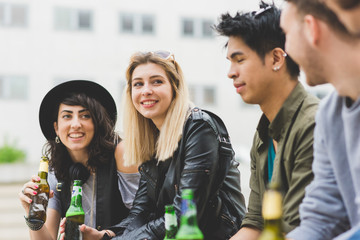 Group of friends multiethnic millennials drinking beer bottle chatting - happiness, leisure, friendship concept