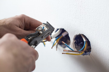 Pliers peeling copper wires. Сloseup on electrician hands, wall sockets in the background
