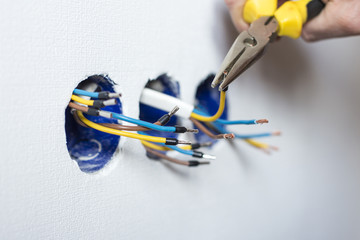 Electrician mounting the wires into electrical wall fixture or socket, closeup on hands and pliers