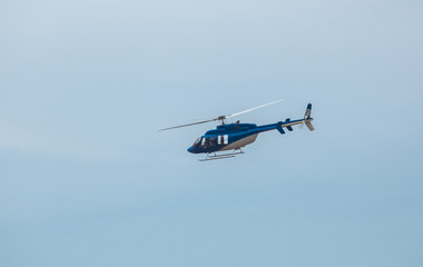 A large, blue helicopter is flying against the blue sky.