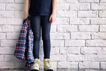 Legs of cute stylish girl near light brick wall