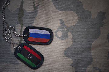 army blank, dog tag with flag of russia and libya on the khaki texture background. military concept