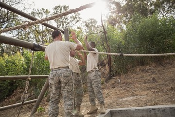Young military soldiers giving after rope climbing