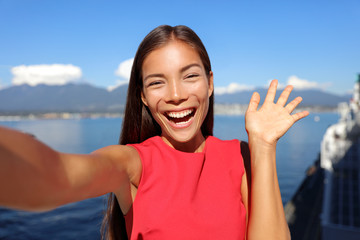 Asian woman talking on video chat mobile phone app or taking selfie photo for social media. Young businesswoman using smartphone smiling happy in sunny outdoors. Urban female professional.