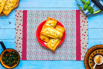 Delicious pie with spinach, made at home, on a wooden background,