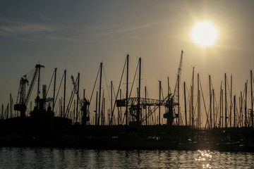 Shape of boat masts and cranes at sunset in Toulon port, France