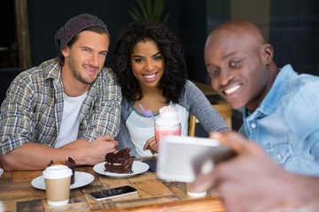 Man with friends taking selfie at wooden table in coffee shop