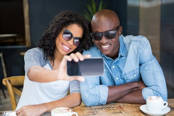 Couple taking selfie with smart phone in coffee shop