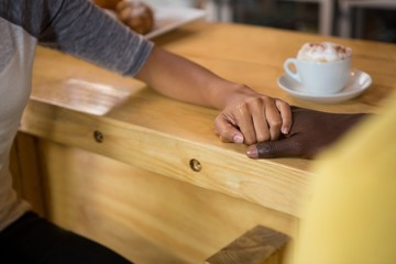 Multi ethnic couple holding hands in coffee house