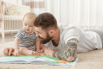 Handsome tattooed young man playing with cute little baby at home