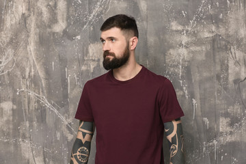 Handsome tattooed young man on gray background