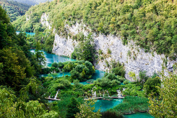 Plitvice Lakes, Croatia, Europe. tourists walking on the pier in the middle of the turquoise lakes