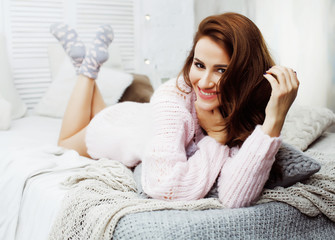 young pretty brunette girl laying in cozy bed with coffee wearing wool winter sweater happy smiling, lifestyle people concept